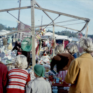 Människor trängs vid ett marknadsstånd.