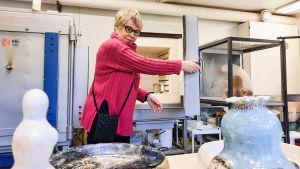 En kvinna i pink tröja öppnar dörren till en keramikugn. Framför henne på bordet står keramik.