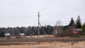 En elstolpe mitt på en åker.