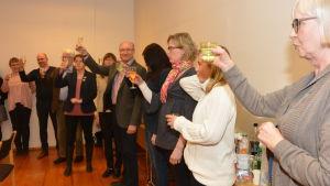 Flera människor står och skålar med champagneglas i händerna.