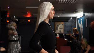 Person med långt ljust hår tittar bestämt rakt fram med mycket rak hållning, bilden tagen i profil.