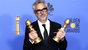 Alfonso Cuarón poserar med sina två Golden Globe-pris.