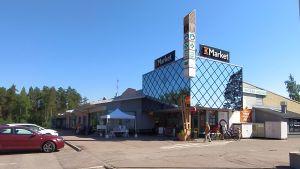 Butiksbyggnad med stort glasverk, parkeringsplats.