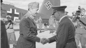 Hitler och Mannerheim skakar hand på flygfältet med ett tyskt plan i bakgrunden.