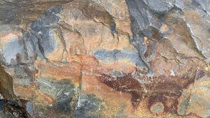 Luonnonkiven sileä mutta polveileva, siniharmaa, oranssi, sininen, keltainen kaunis, maalauksenomainen pinta. Kuin abstrakti maalaus tai kuva tähtisumusta.