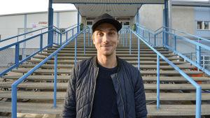 Erik Riska står nere vid trapporna som leder upp till en ishall. Han ler och tittar in i kameran.