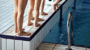Barns fötter vid kanten av en simbassäng.