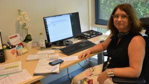 Christa Lindholm sitter vid sitt skrivbord.