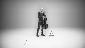 Max Lilja seisoo sellonsa kanssa avarassa tilassa.