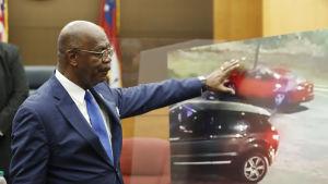 En man i kostym pekar på en plansch med två bilar.