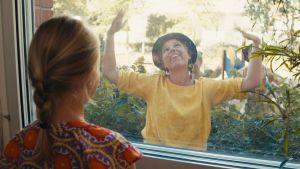 Ett barn tittar ut genom ett fönster på en kvinna som dansar