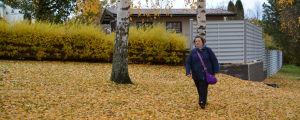 Riikka Laine promenerar i parken bland orange höstlöv.