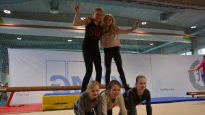 Flickor står i pyramid under gymnastiklektion.