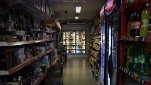 En gång i en livsmedelsbutik. På hyllorna skymtar olika varor och i slutet av gången finns en kyl fylld med produkter.