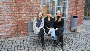 Ellen Wilenius, Julia Nummenmaa och Catharina Walldén sitter på en bänk utanför Arken