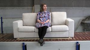 Nainen istuu sohvalla huonekalutehtaalla.