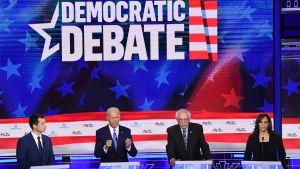 Tre män och en kvinna står på rad och debatterar.