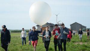 Fyra personer bär på en väderballong, som ska släppas upp vid Meteoria Söderfjärden.