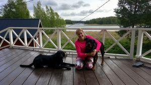 Simona Lilius-Lappalainen med sina hundar på terassen