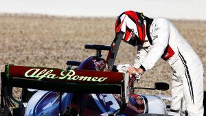 Kimi Räikkönen lutar mot sin bil.