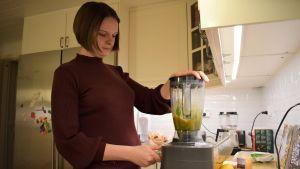 Rebecca Börman manövrerar en matblender i köket.