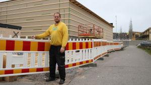 En man i gul tröja står utomhus vid ett bygge. Röd-gult staket runt bygget.