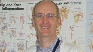 Hälsocentralläkare John Shaw med en plansch över olika ben/skelettdelar i bakgrunden.