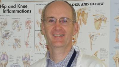 Hälsocentralläkare John Shaw med en plansch över olika ben skelettdelar i  bakgrunden. 376a7a8929579