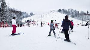 Många människor i snöig slalombacke.
