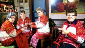 Fyra kvinnor klädda i korsnäströjor arbetar på korsnäströjor.