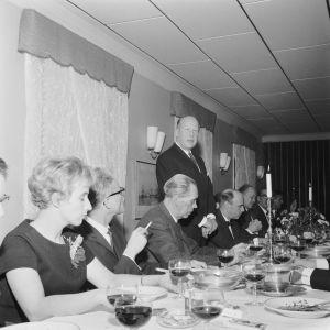 Ett antal personer vid ett middagsbord. En man håller tal. Mannen heter Sven Högström.