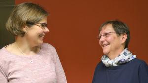 Sanna Nyman och Harriet Ekholm framför en röd vägg