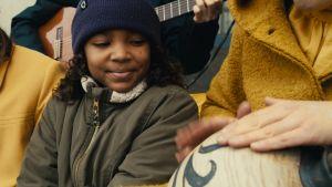 En flicka tittar på en person som spelar på en afrikansk trumma