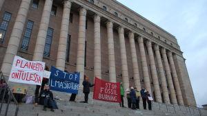 Klimatdemonstranter med banderoller på riksdagens trappa.