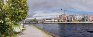 Maisema Tampereen Näsinpuiston Mältinrannasta, etualalalla puistonpenkkejä, koski, taustalla kerrostaloja