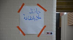 Ett vitt papper med text på arabiska tejpad med orangefärgad tejp på en vit tegelvägg.