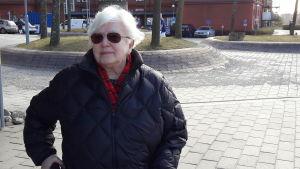 Aino Wikström, med solglasögon, tittar mot kameran, håller i rollator, ler.
