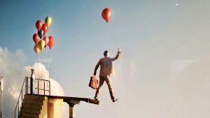 Detalj ur den svenske fotografen Erik Johanssons utställning på Fotografiska i Tallinn där en man med en ballong i handen tar ett steg ut över kanten på ett högt hopptorn.
