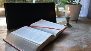 Uppslagen bibel och ett tänt ljus vid en radio.