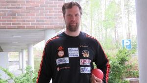 En man med lite lockigt mörkt hår och skägg  och tröja med mycket reklamtext. Han håller en röd kula i ena handen. Han är kulstötare och poserar framför kameran.