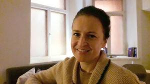 Anne Teir-Siltanen framför två fönster.