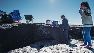 Nainen ja mies kalliolla, osoittavat tavaroita: muovipakeissa ruokatarpeita, vesisäiliöitä ja kottikärryjä.