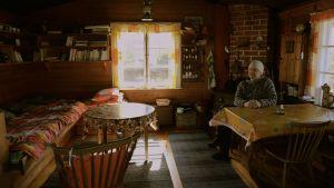 Pienen mökin tupa, jossa on vasemmalla puolella sänky, keskellä pieni pyöreä pöytä ja pieni keinutuoli ja oikealla seinustalla ruokapöytä kahdelle. Ruokapöydän ääressä istuu mies. Takaseinällä olevasta ikkunasta tulvii valoa sisälle.