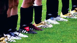 Jalkapalloilijoiden jalkoja rivissä Alandia Cupissa.