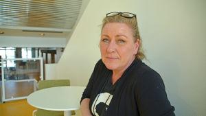 Kvinna som sitter vid ett cafébord.