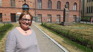 Kvinna framför rött tegelhus.