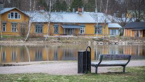 En parkbänk och skräpkorg vid stranden, ett gult hus fasad speglas i vattenytan