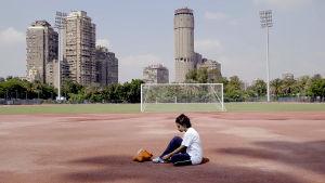 Amal -tyttö istuu urheilukentällä