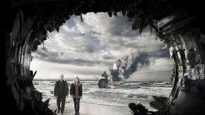 Mies ja nainen hiekkarannalla jonkinlaisen tunnelin päässä.