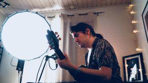 Musikern André Linman spelar gitarr under starkt ljus hemma hos sig.
